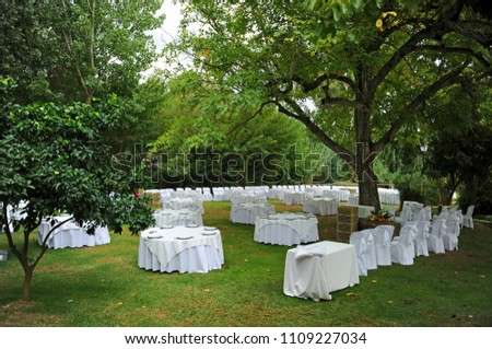 Tables prepared for the celebration of a romantic wedding banquet in an outdoor garden #1109227034