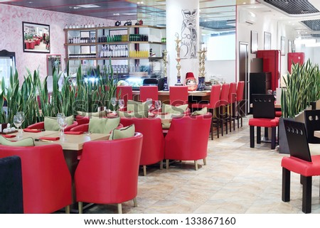 Tables, red armchairs and bar counter in small modern Japanese restaurant.