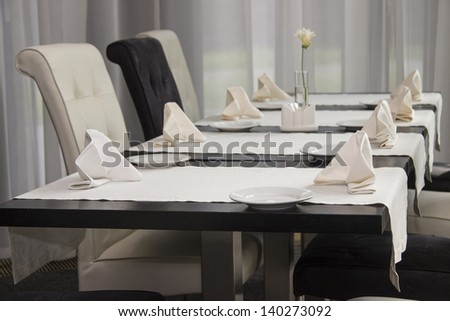 Tables set for meal in modern restaurant