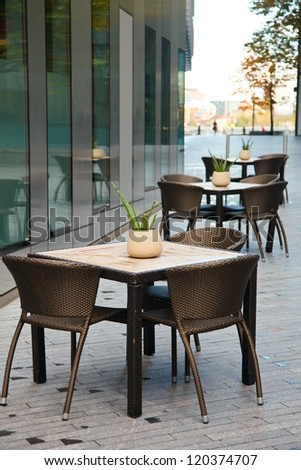 Tables with chairs of a sidewalk cafe beside office building in London