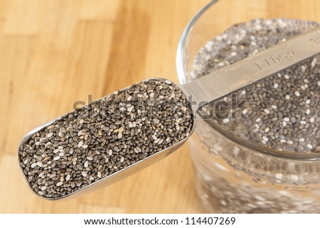 Tablespoon of chia seeds with chia seeds soaking in a glass of water