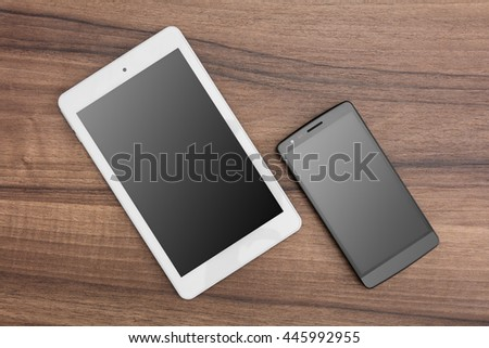 Tablet and mobile phone on wooden desk