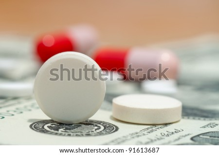 Tablet and pills on the 100 dollars banknote