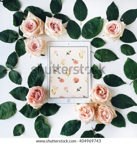 Tablet and pink rose flower with green leaves on white background. Top view, flat lay