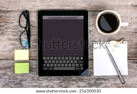 tablet as a keyboard glasses pen note paper calculator  with keyboard on screen on wood backgound