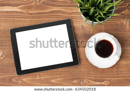 Tablet computer and coffee on wooden background
