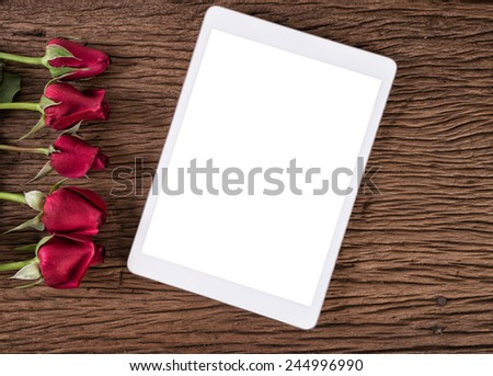 Tablet computer and red rose on old wooden background