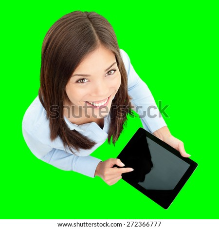 Tablet computer. Business woman using digital tablet computer PC happy isolated cutout on green background. Focus on both tablet and face. Woman in business shirt with finger on touch screen display. stock photo