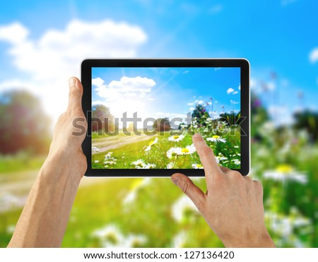 tablet computer in hand for advertisement. field  background