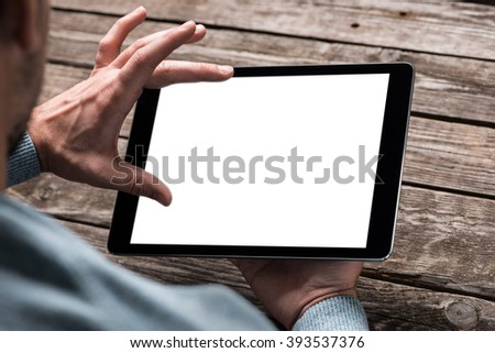 Tablet computer  in male hands over table. Clipping path included. stock photo