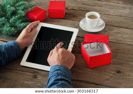 Tablet computer in men hands. Near the table with tablet computer open red gift box, a cup of espresso coffee and fluffy Christmas tree branch Free space for text. top view. Copy space. Closeup
