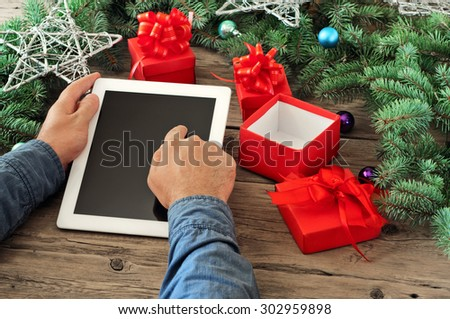 Tablet computer in men hands. Near the table with tablet computer open red gift box, christmas toys, stars and fluffy fir branches. Free space for text. top view. Copy space. Closeup