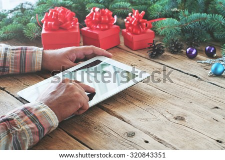Tablet computer in men hands. Near the table with tablet computer red gift box, christmas toys and fluffy fir branches. Free space for text. top view. Copy space. Closeup