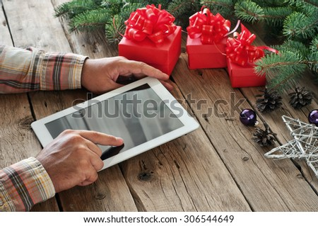 Tablet computer in men hands. Near the table with tablet computer three gift boxes, christmas toys, stars , fir cones and fluffy fir branches. Free space for text. top view. Copy space. Closeup