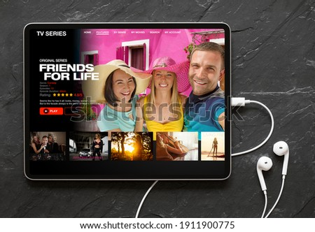 Tablet computer with earphones on black background showing movie and TV shows online streaming service app on the screen