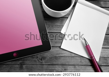 Tablet empty pink screen with notepad on desk