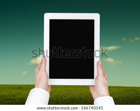 Tablet hand held in a vertical position against the background of meadows and sky
