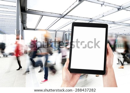 tablet in the hands and the crowd of people in the background