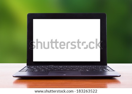 Tablet laptop with white blank screen on wooden table, front view, green natural background.