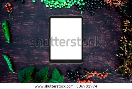 Tablet (4:3) mockup on frame frame with berries, leaves, red currant, green peas, barberry and apple on vintage wood table