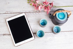 Tablet on wooden table with tea cups