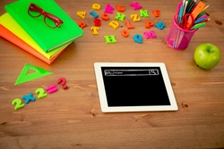 Tablet PC and school items on wooden desk in class. Education concept. Top view