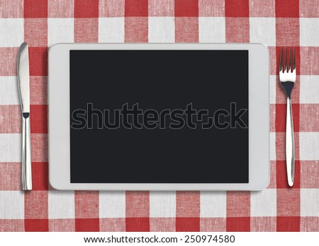 tablet pc looking like ipad, fork and knife on red checked tablecloth