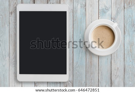 Tablet pc looking like ipad on table with coffee top view #646472851