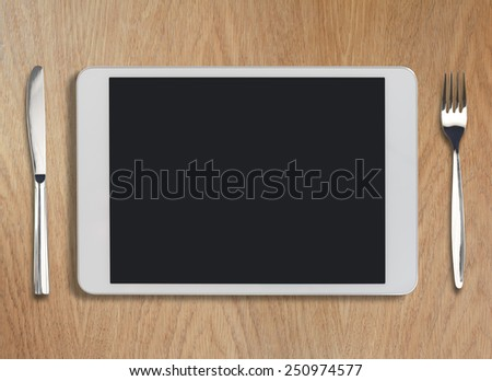 tablet pc looking like ipad on wooden table with fork and knife