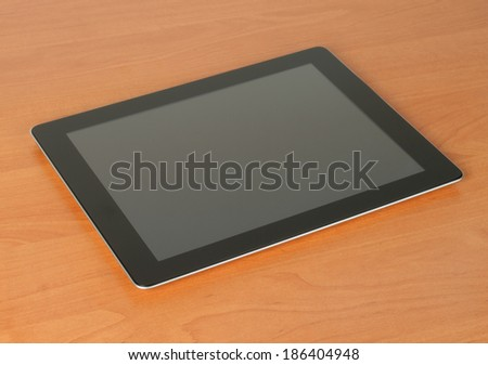 Tablet PC on wooden background close-up