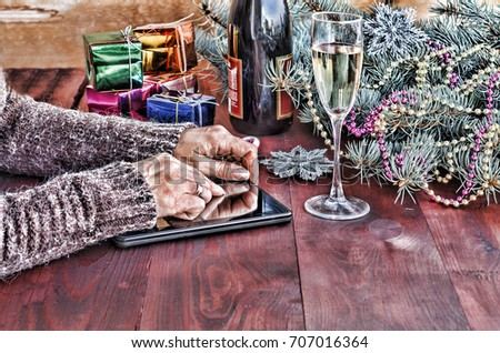 tablet PC. Tablet PC in the hands of women. At the table with a Tablet PC Gold, red, blue, green colorful gift box, Christmas toys and fluffy fir branches. Free space for text. Closeup #707016364