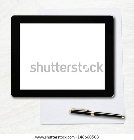 Tablet pc with blank screen and pen over table.