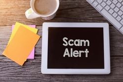Tablet pc with Scam Alert and a cup of coffee on wooden background