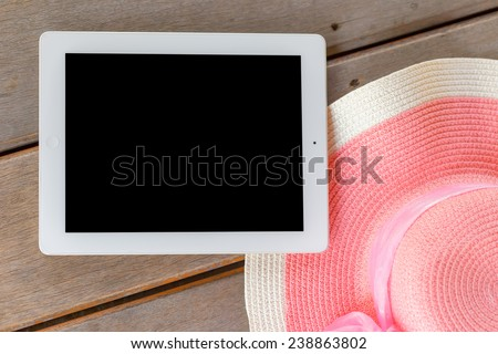 Tablet white frame and black screen  with  Beautiful woman\'s hat on wooden floor in  summer theme