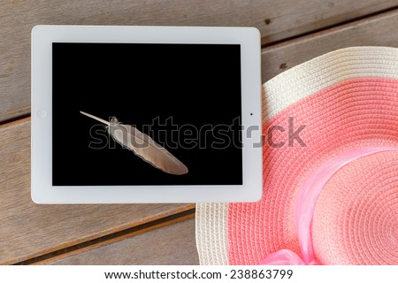 Tablet white frame and black screen  with feather and Beautiful woman\'s hat on wooden floor in  summer theme