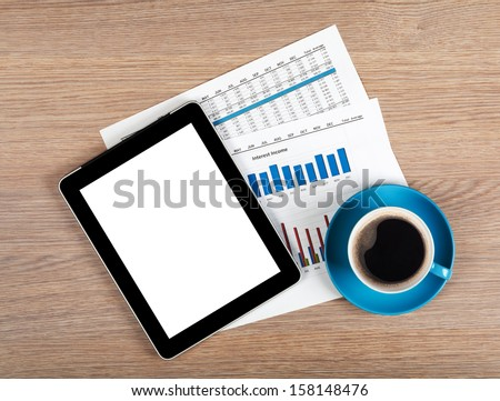 Tablet with blank screen and coffee cup on office wooden table