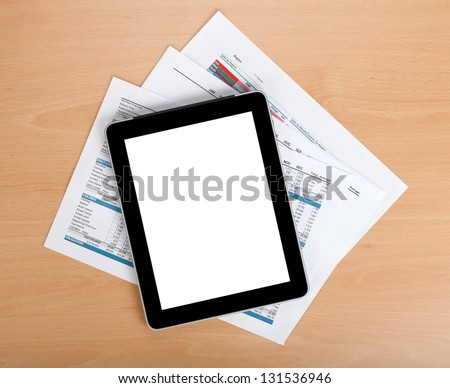 Tablet with blank screen over papers with numbers and charts. View from above