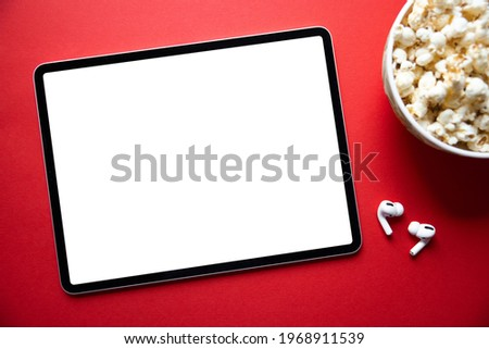 Tablet with empty white screen with wireless earphones and bowl of popcorn next to it. Mockup for video or movie screenshot.