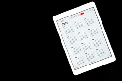 tablet with open calendar for 2021 year isolated on a black background. space for text