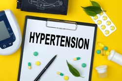 Tablet with text HYPERTENSION. Nearby is a tonometer, medicines, vitamins and a pen. Medical concept.