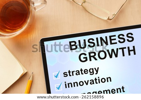 Tablet with words business growth. Business concept.