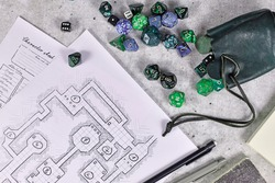 Tabletop role playing flat lay with RPG game dices, character sheet,dungeon map and pen on wooden desk