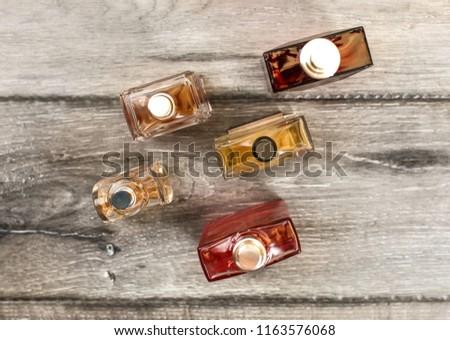 Tabletop view, men fragrances colourful  bottles, on wooden boards desk. #1163576068