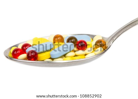 Tablets and capsules on the spoon on white