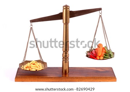 Tablets and fresh vegetables on a isolated scale