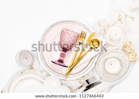Tableware and decorations for serving a festive table.  Plates, wine glasses and cutlery with  decorative textile on white background. #1127466443