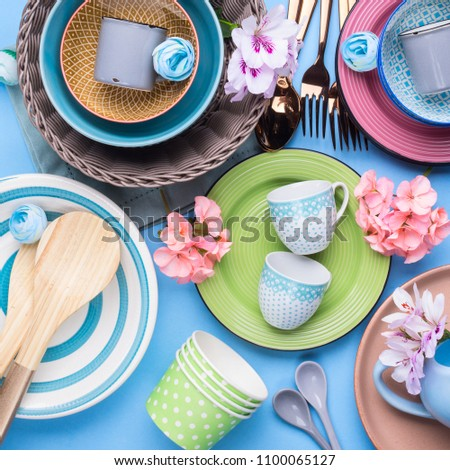 Tableware dish set on blue pastel background with flowers. Flat lay #1100065127