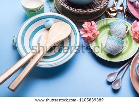 Tableware dish set on blue pastel background with flowers. Flat lay #1105839389