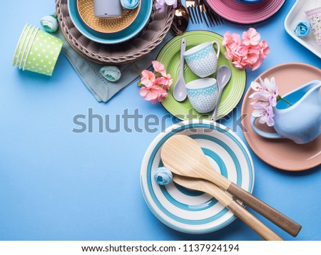 Tableware dish set on blue pastel background with flowers. Flat lay #1137924194