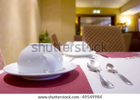 Tableware for a breakfast at an empty restaurant (white coffee cup and spoons)